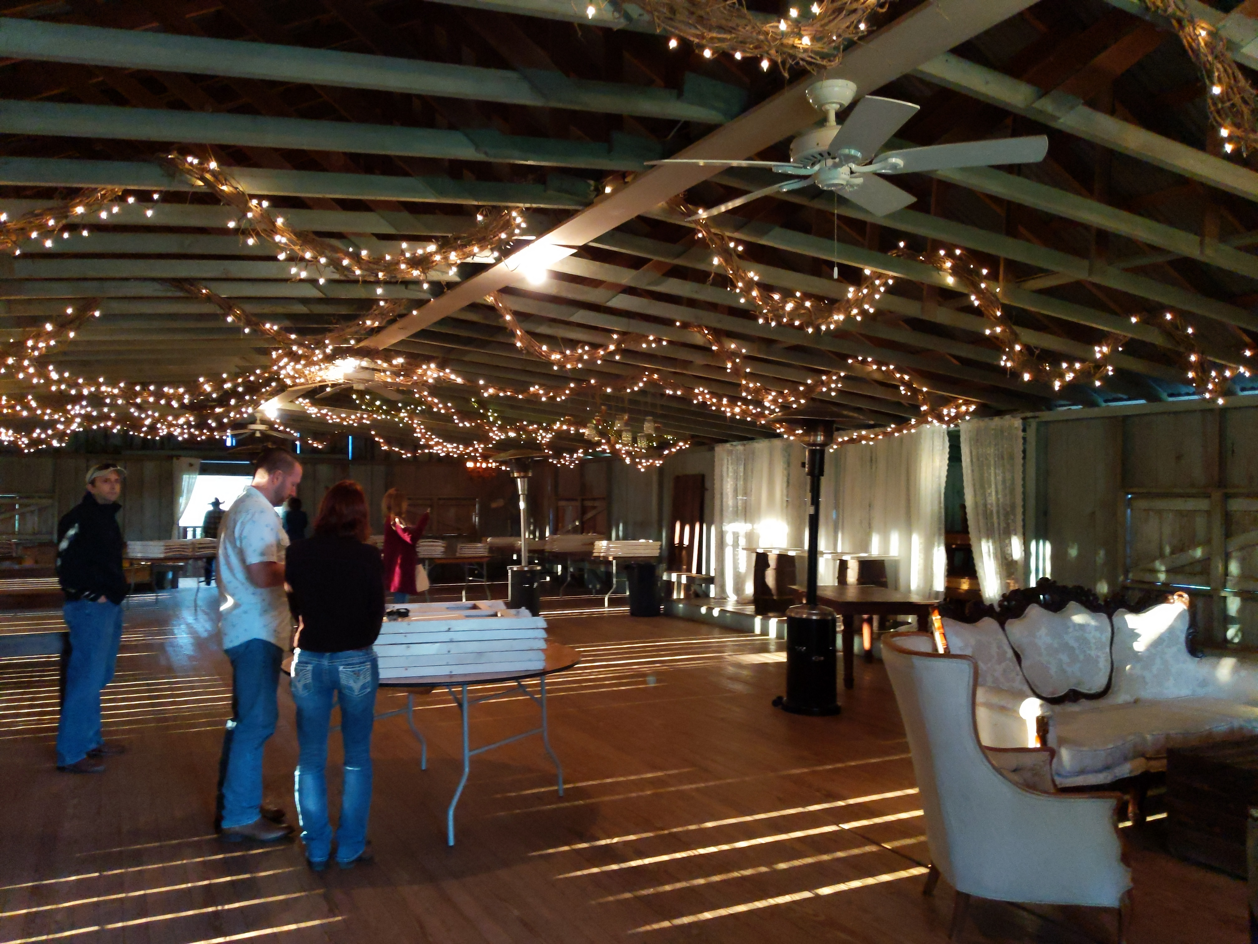 Venue wood floor with couch reception and tables set for wedding. Small white lights draped over the exposed ceiling beams