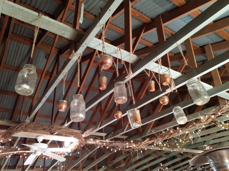 Mason jars hung as decoration from ceiling beams amid white lights