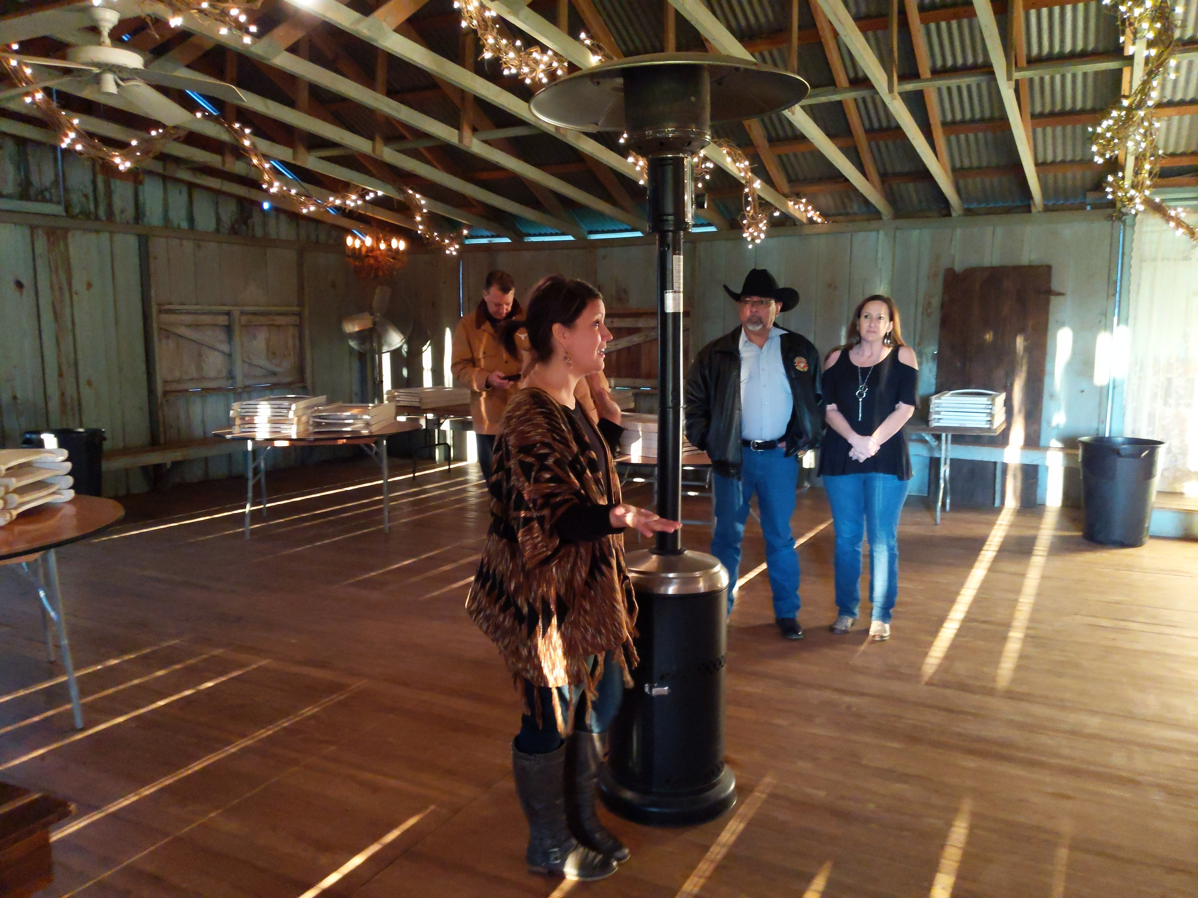 Amber Burris talking to tour group in the hall as she points to where she used to stack hay in earlier days