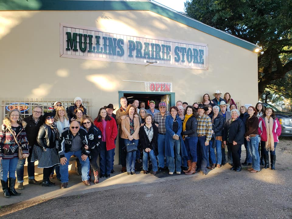 People posing in front of store front Mullins Prairie Store